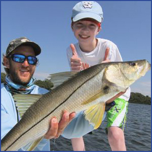"Fisher Adkisson and I hold up this beautiful 35"" snook"
